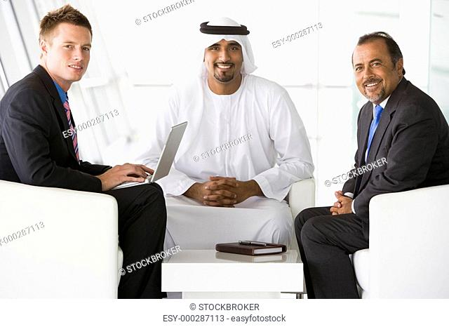 Three businessmen indoors with a laptop smiling high key/selective focus