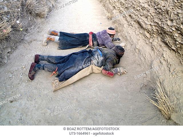Tibetan pilgrims prostrating their way around Labrang monastery in Xiahe, Gansu during the Tibetan new year