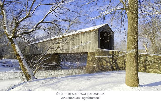 A wooden covered bridge covered in snow, Pennsylvania, USA