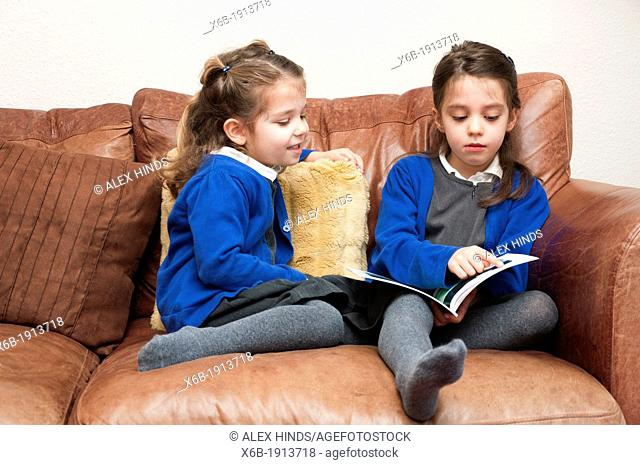 Young sisters in Primary School uniform reading a book together