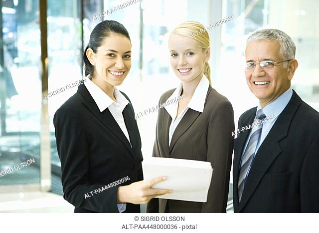 Business associates smiling at camera, one woman holding stack of documents