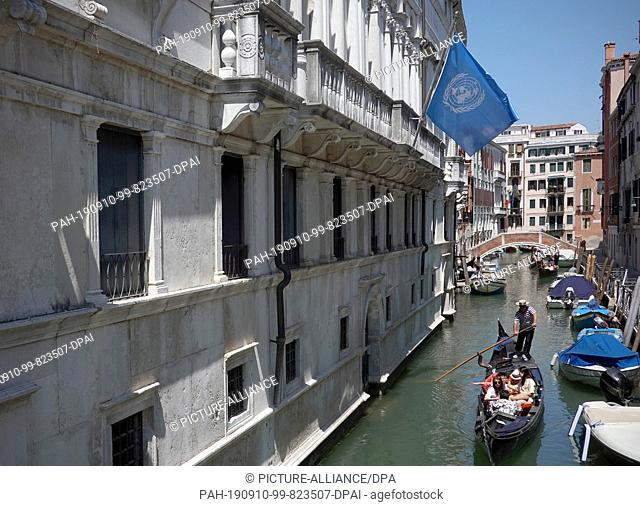 18 June 2019, Italy, Venedig: Gondoliere drive with their boats on a canal between the houses of the city. Above them the flag of the United Nations (UN) flies