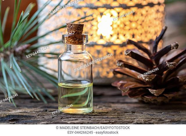 A bottle of essential oil with pine branches and cones in the background