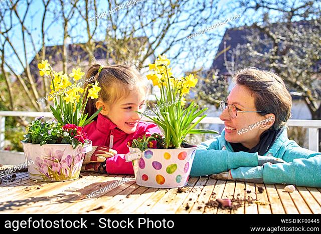 Mother and daughter planting flowers on balcony