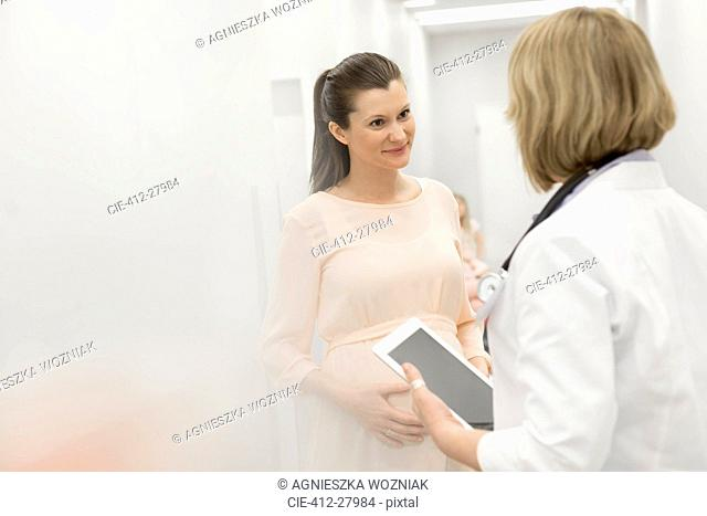 Doctor with digital tablet talking to pregnant patient in clinic corridor