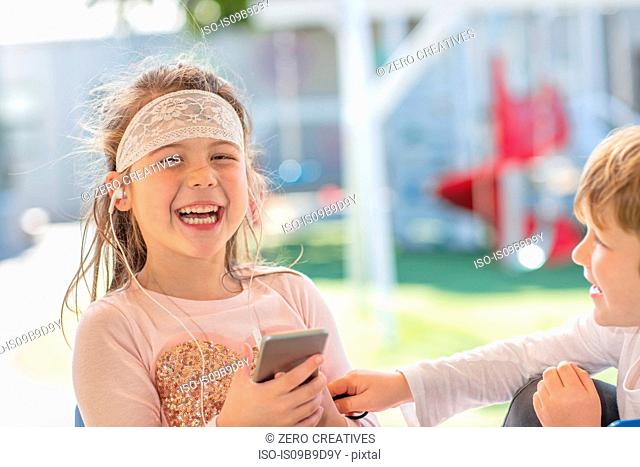 Young girl holding smartphone, wearing earphones, laughing