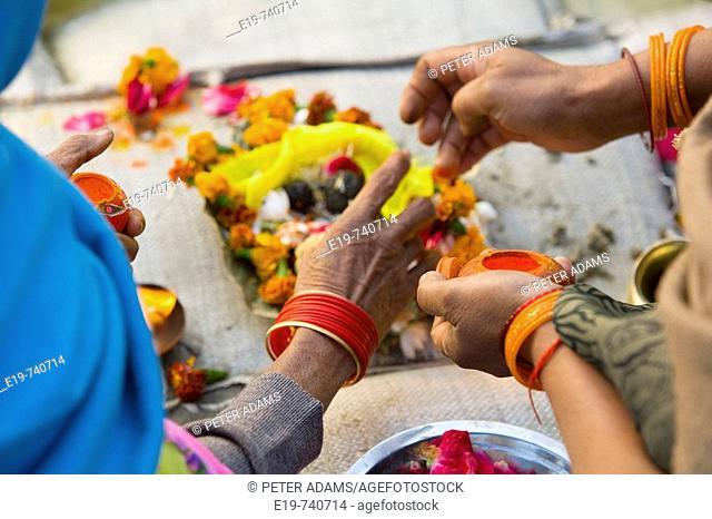 Preparing for puja (devotional Hindu practise) by river Ganges at Kumbh Mela festival. Allahabad, Uttar Pradesh, India