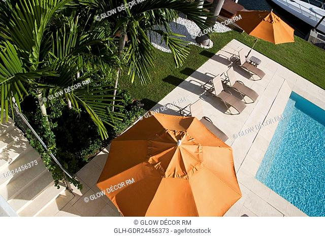 Patio umbrellas with lounge chairs at the poolside