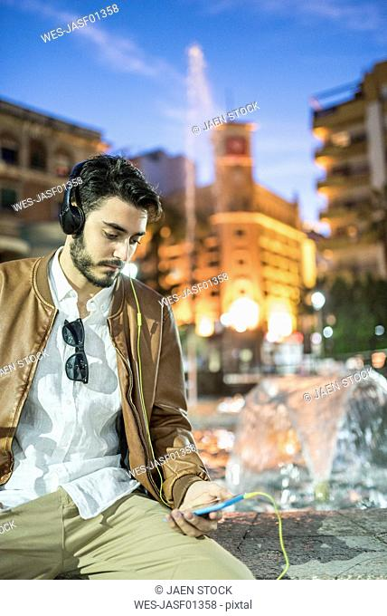 Man with headphones and cell phone at a fountain at night