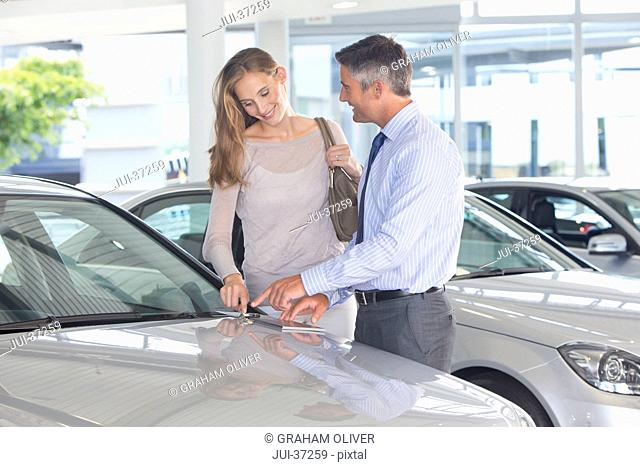 Salesman and customer looking at color swatch on automobile hood in car dealership showroom
