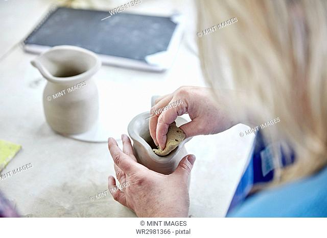 A woman using her hands to shape and smooth a wet clay jug to match another, making a pair