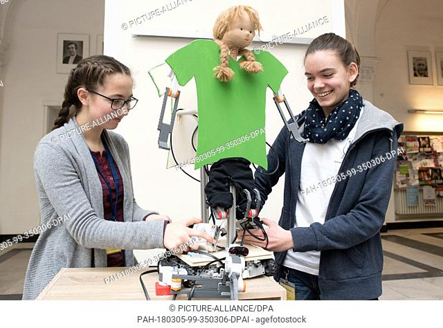 05 March 2018, Germany, Hanover: 15-year-old students from Langenhagen Gymnasium Anna-Katharina (l) and Ricarda present a robot they constructed at the 'RoboCup...