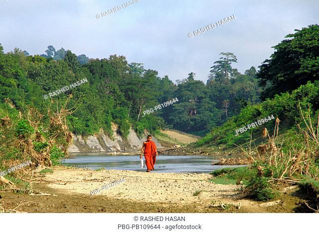 A monk walks at the bank of Sangu River at Thanchi Bandarban, Bangladesh November 2010