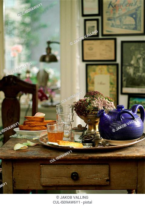 Vintage tray on desk with glasses of tea and teapot