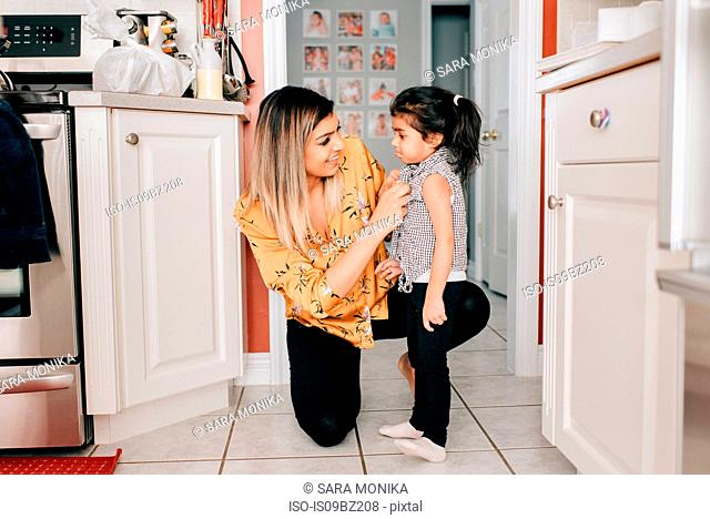 Girl's mother fastening her blouse buttons in kitchen