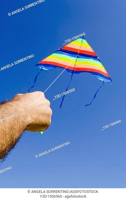 Man's hand holding a kite againste the blue sky