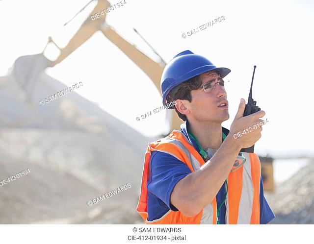 Worker using walkie-talkie in quarry