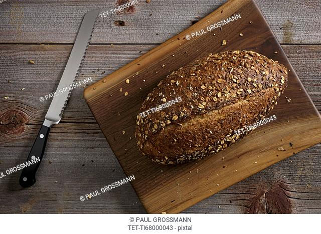 Kitchen knife and loaf of bread on wooden table