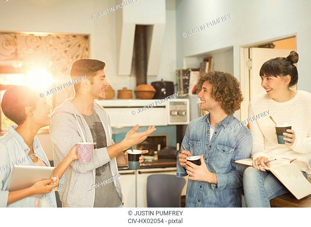 Young adults hanging out talking drinking coffee