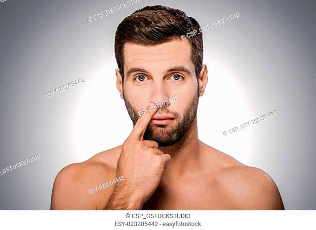 Digging for gold. Portrait of handsome young shirtless man picking his nose while standing against grey background