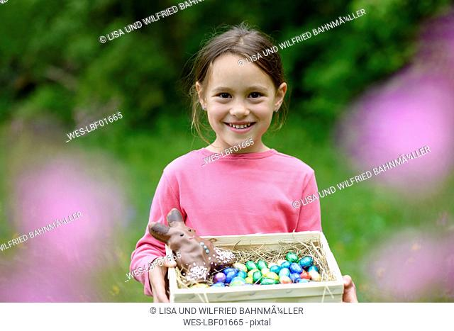 Portrait of happy little girl holding Easter nest