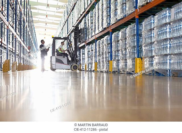 Workers with forklift in bottling warehouse