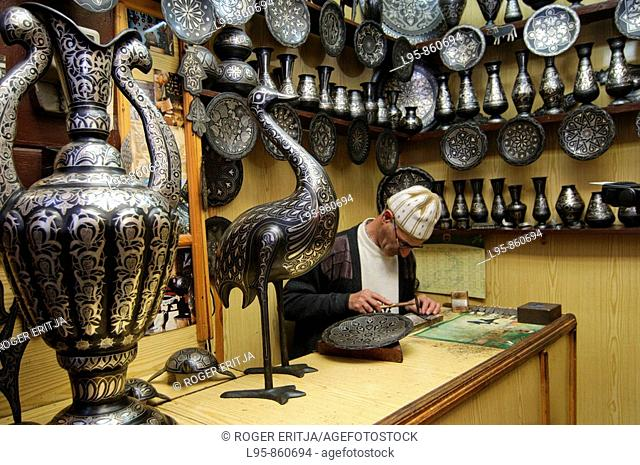 Working in silver covered crafts handwork at a shop in Fez, Morocco