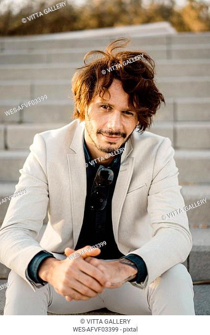 Portrait of businessman sitting on stairs outdoors