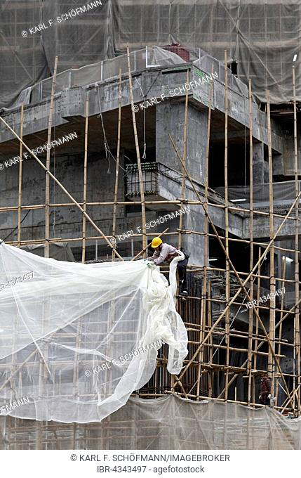 Workers attached a tarpaulin to a scaffolding of bamboo, high-rise building under construction, Tsim Sha Tsui, Kowloon, Hong Kong, China