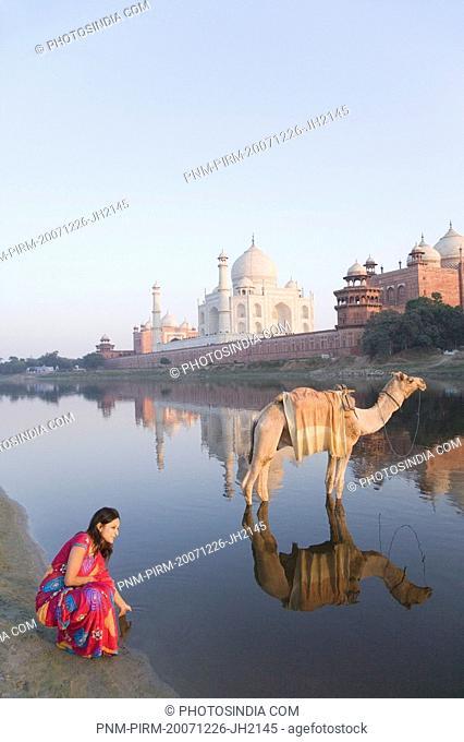 Woman at the riverbank with mausoleum in the background, Taj Mahal, Yamuna River, Agra, Uttar Pradesh, India