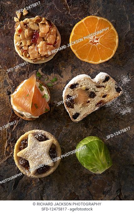 Various Christmas dishes, fruits, and winter vegetables on a rusty surface