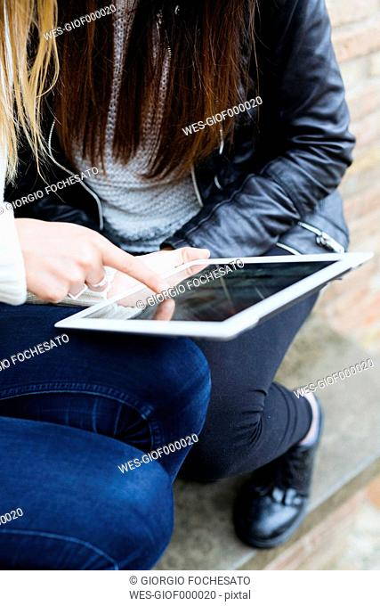 Two young women using digital tablet, close-up