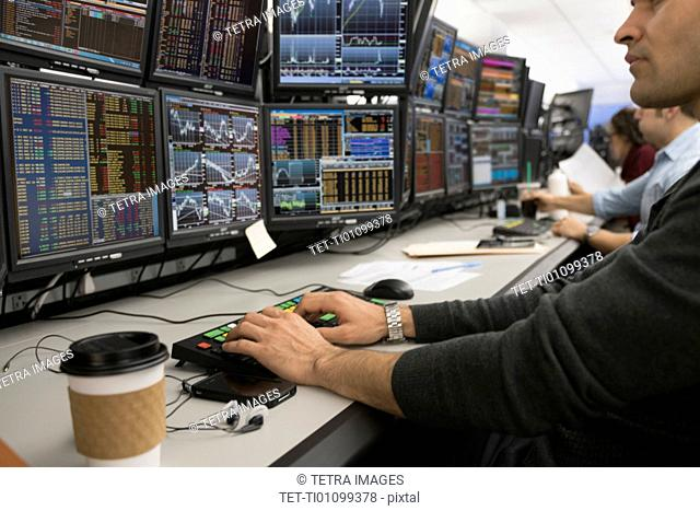 Young trader typing on computer