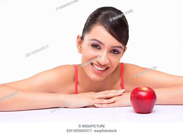 Portrait of smiling young woman with apple over white background