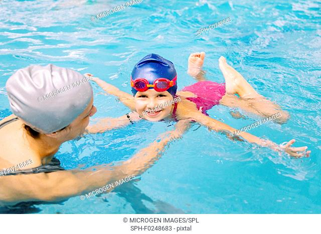 Swimming class. Little girl learning to swim with swimming instructor
