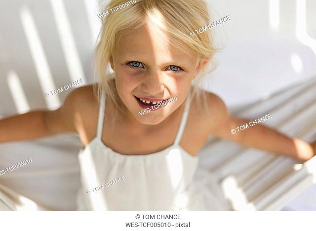 Portrait of smiling little girl with tooth gap in a hammock