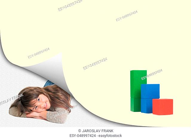 Page with curl effect and smiling cute little girl lying in an exposed corner looking at the camera. Colorful graph of wooden cubes is ready for your text