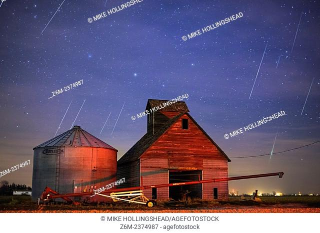 Geminid meteors streak across the sky behind a barn in western Iowa