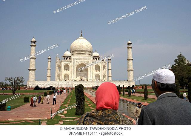 Kashmiri couple viewing at Taj Mahal Seventh Wonders of World on the south bank of Yamuna river , Agra , Uttar Pradesh , India UNESCO World Heritage Site