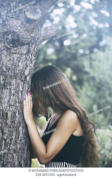 Depressed young woman leaning against a tree crying