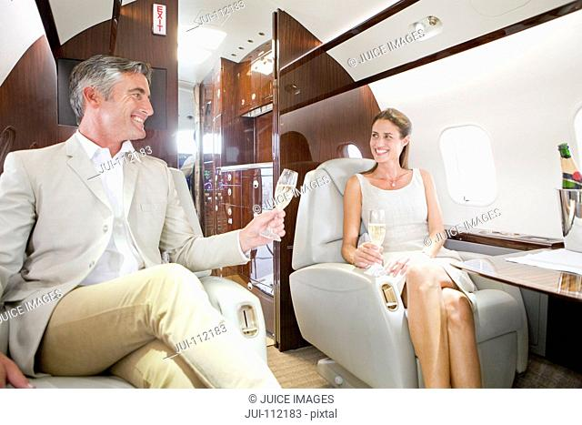 Attractive couple drinking champagne on private jet