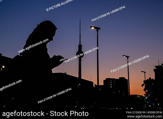 08 September 2021, Berlin: A woman looks at her mobile phone in the evening in front of the Berlin TV tower on Karl-Marx-Allee