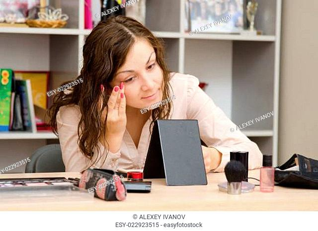 Girl puts foundation on face at work