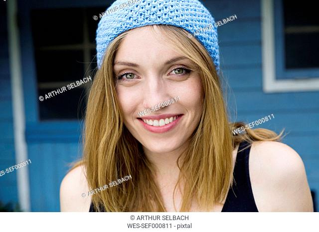 Portrait of a smiling young woman wearing light blue bonnet