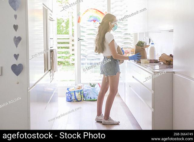 young woman coming in her house with the groceries, she wears mask and gloves