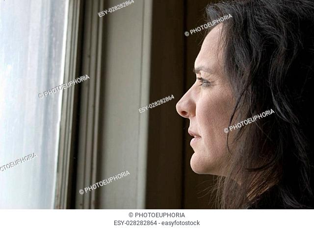 Thirty-eight year old impoverished woman looking out window of low income home