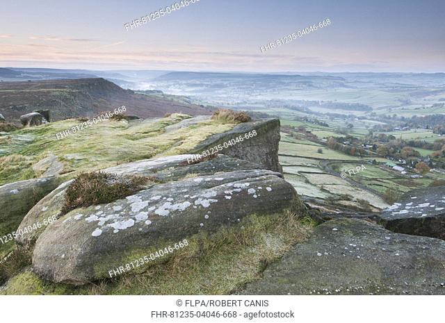 View of rocks and moorland across valley in frost at sunrise, Curbar Gap, Dark Peak, Peak District N.P., Derbyshire, England, November