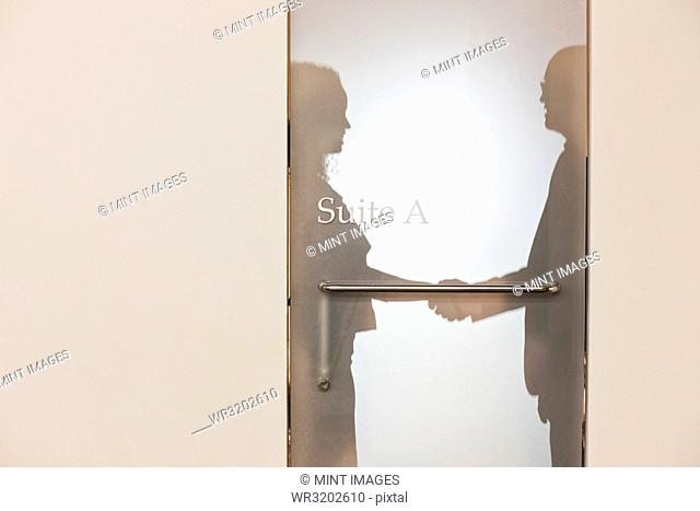 Two business people shaking hands and silhouetted through the frosted glass door of an office suite