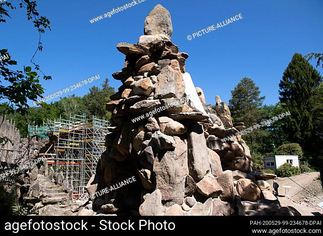 29 May 2020, Saxony, Gablenz: A scaffold surrounds the Rakotzbrücke behind the grotto in the Rhododendron Park. Inaugurated on the same day