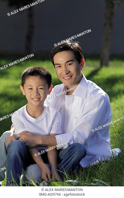 Father and son sitting on grass together smiling